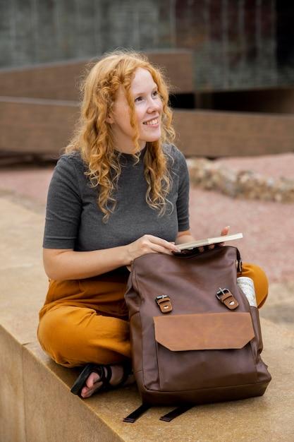 Mulher com mochila segurando um diário Foto gratuita