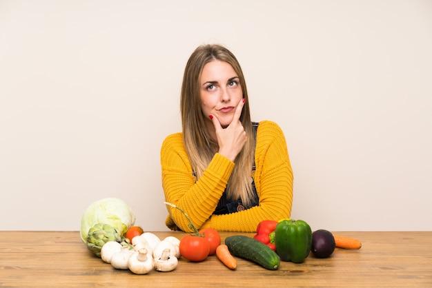 Mulher com muitos legumes em pé e pensando uma idéia Foto Premium
