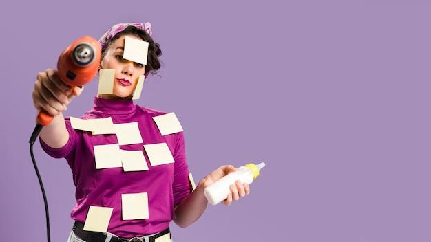 Mulher com notas auto-adesivas nela segurando a broca e mamadeira Foto gratuita
