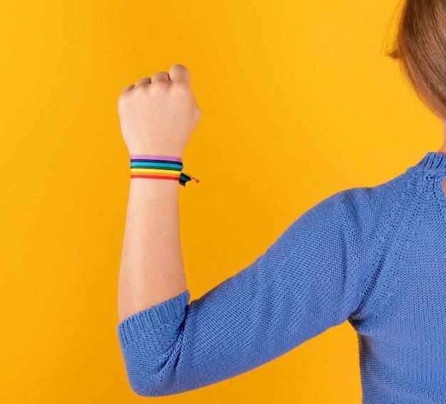 Mulher com o braço levantado e bandeira do orgulho gay Foto Premium