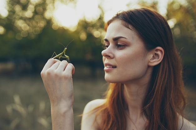 Mulher com o inseto na mão orando árvores natureza mantis verão. Foto Premium