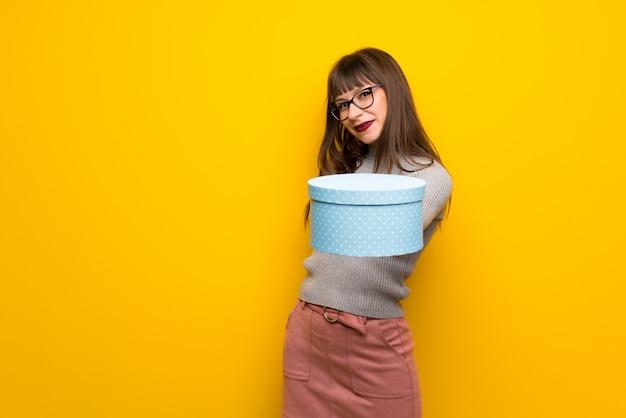 Mulher, com, óculos, sobre, parede amarela, segurando, um, presente, em, mãos Foto Premium