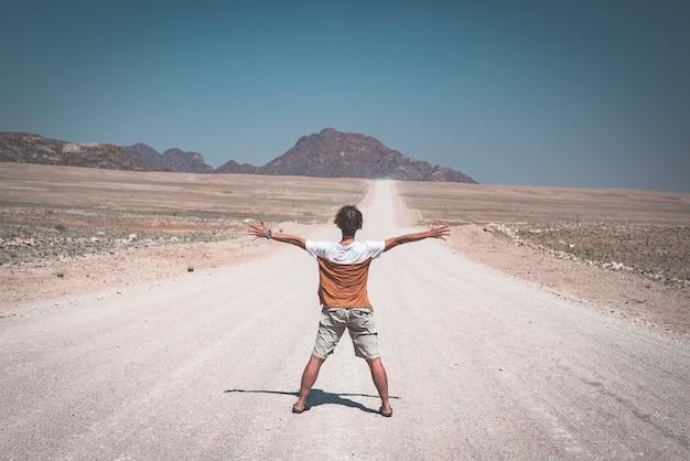 Mulher com os braços estendidos em pé na estrada de cascalho, cruzando o deserto do namibe, no namib naukluft national park, principal destino de viagem na namíbia, áfrica. vista traseira, imagem enfraquecida. Foto Premium