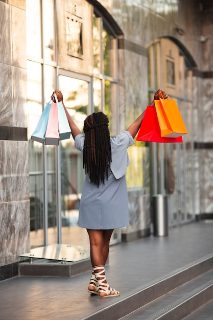Mulher com os braços levantados com sacolas de compras Foto gratuita