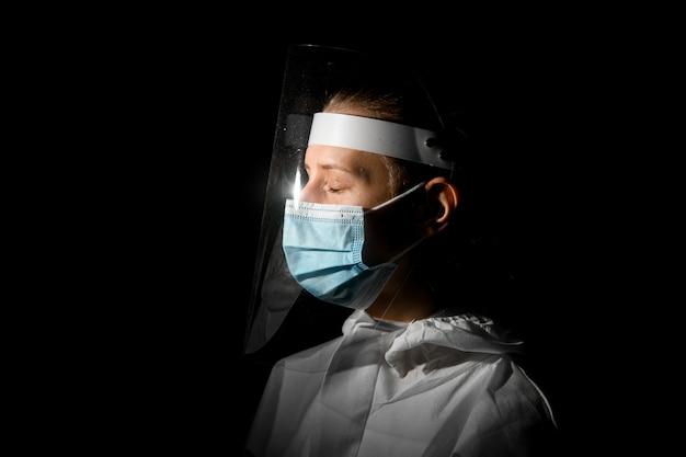 Mulher com os olhos fechados na máscara médica e escudo protetor na cabeça Foto Premium