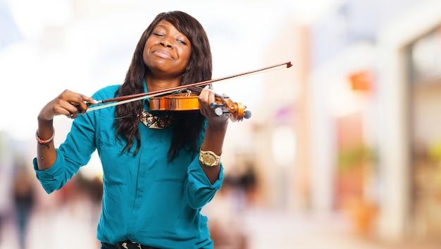 Mulher com os olhos fechados, tocando um violino Foto gratuita