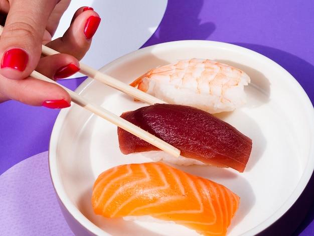Mulher com pauzinhos tomando uma placa de forma de sushi de atum Foto gratuita
