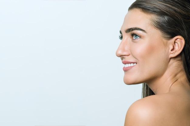 Mulher com pele limpa, maquiagem natural, cabelos lisos e saudáveis Foto Premium