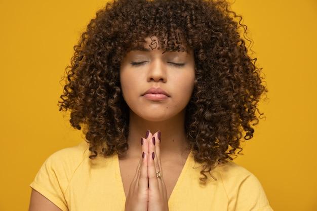 Mulher com penteado afro e blusa amarela Foto Premium