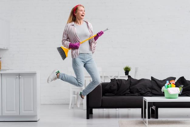 Mulher com pincel pulando em casa Foto gratuita