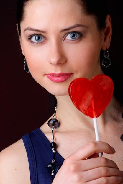 Mulher com pirulito vermelho em forma de coração Foto Premium