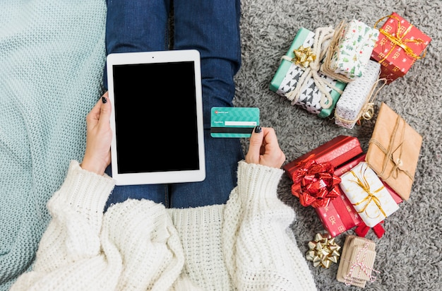 Mulher, com, presentes, e, cartão crédito, com, tabuleta Foto gratuita