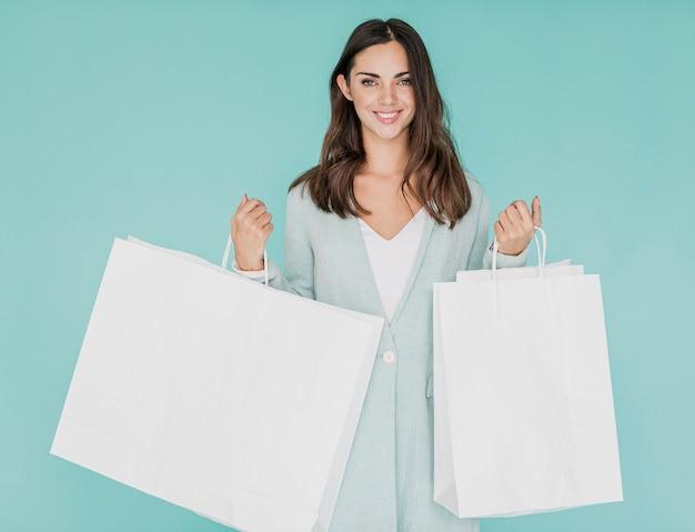 Mulher com redes de compras em fundo azul Foto gratuita