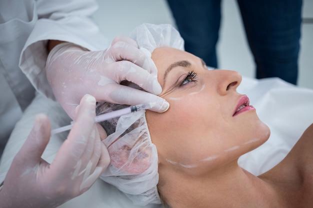 Mulher com rosto marcado, recebendo injeção de botox Foto gratuita
