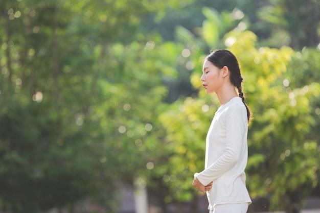 Mulher com roupa branca meditando na natureza Foto gratuita