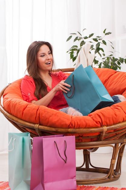 Mulher com sacolas de compras em casa Foto gratuita