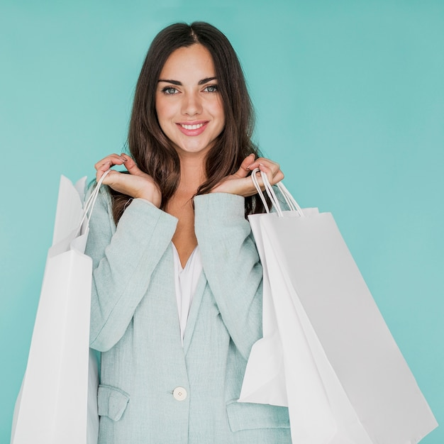 Mulher com sacolas de compras nas duas mãos, posando para a câmera Foto gratuita