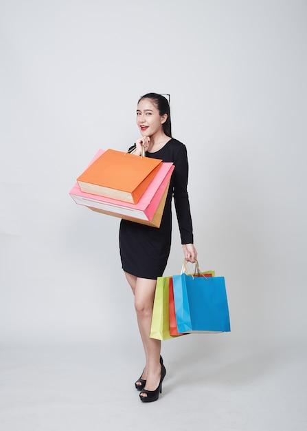 Mulher com sacos de compras em pé no branco Foto Premium