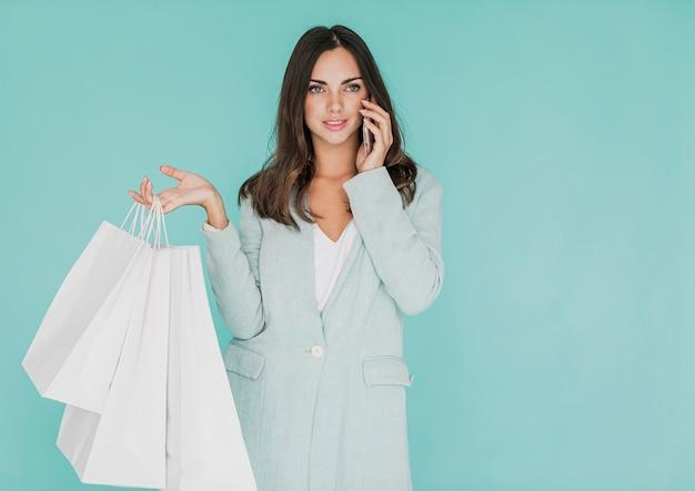 Mulher com sacos de compras, falando ao telefone Foto gratuita