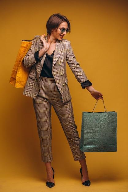 Mulher com sacos de compras no estúdio em fundo amarelo isolado Foto gratuita