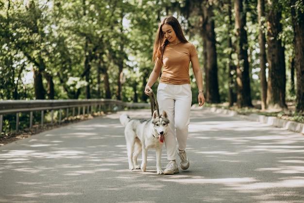Mulher com seu cachorro husky no parque Foto gratuita
