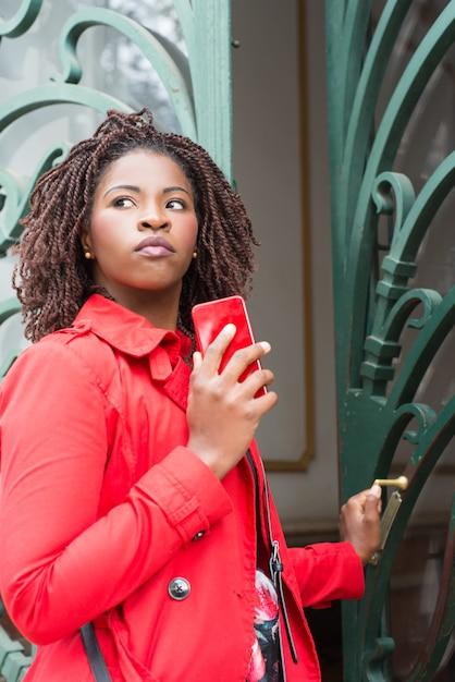 Mulher com smartphone, abrindo a porta e olhando de lado Foto gratuita