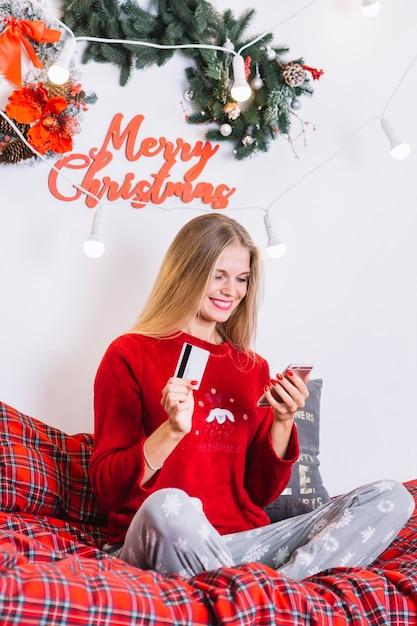 Mulher, com, smartphone, e, cartão plástico, cama Foto gratuita