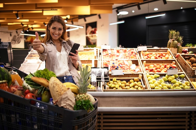Mulher com smartphone em um supermercado em pé perto das prateleiras cheias de frutas na mercearia segurando o polegar para cima Foto gratuita