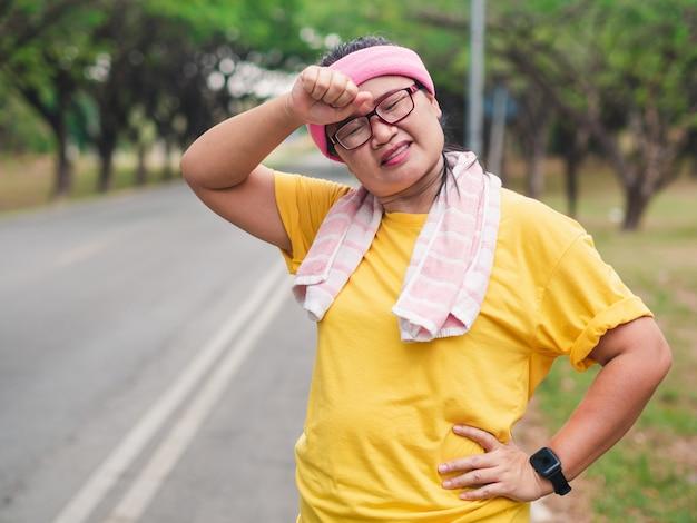 Mulher com sobrepeso se sentindo cansada enquanto corre no parque. conceito de perda de peso Foto Premium