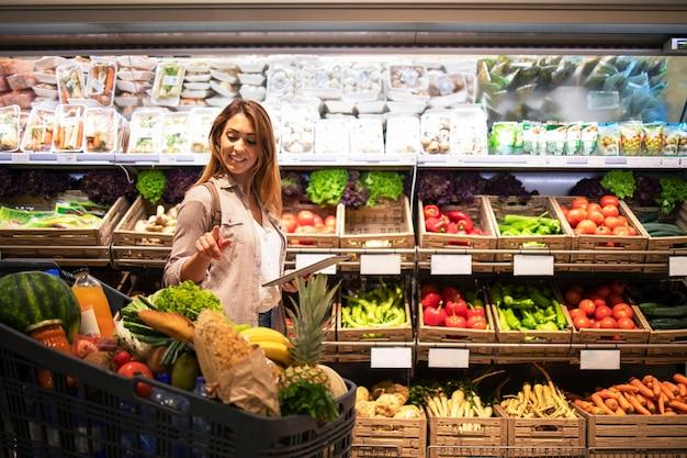 Mulher com tablet verificando o carrinho de compras para ver se tem tudo o que precisa para o almoço Foto gratuita