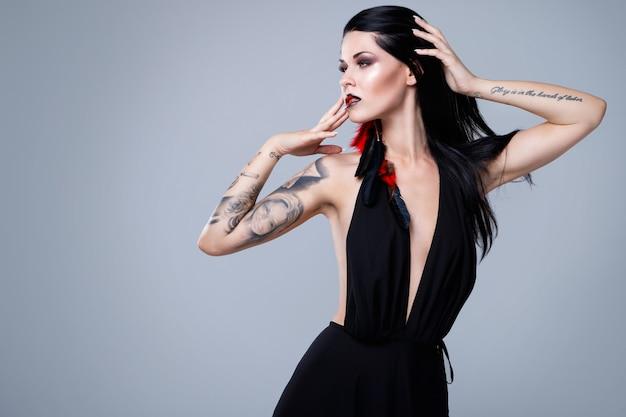 Mulher com tatuagens usando vestido preto Foto Premium