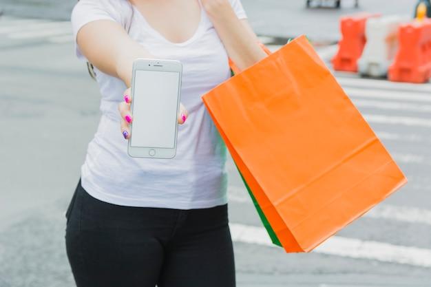 Mulher, com, telefone, e, bolsas para compras Foto gratuita