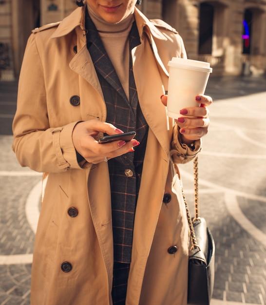 Mulher com telefone e café na praça da fonte Foto gratuita