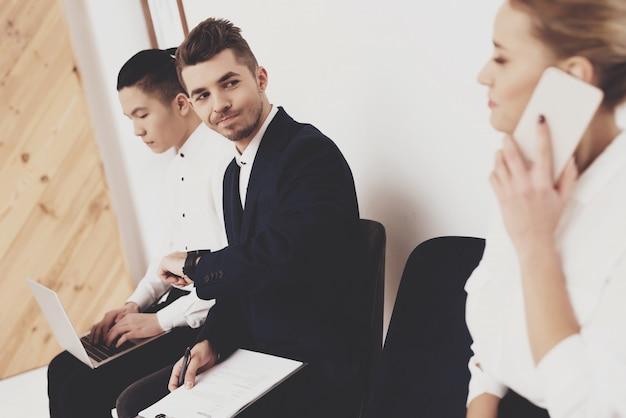Mulher com telefone está sentado com colegas de trabalho. Foto Premium