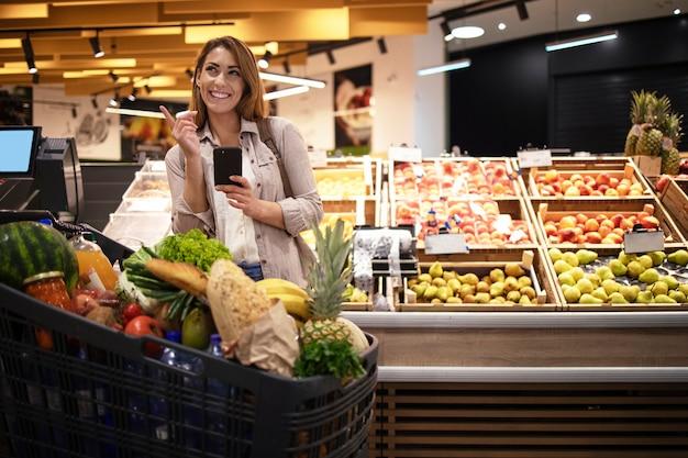 Mulher com telefone inteligente em um supermercado parado perto das prateleiras cheias de frutas no supermercado Foto gratuita