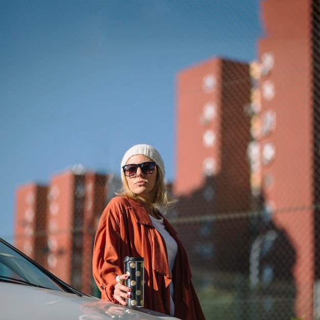 Mulher com thermos perto do carro Foto gratuita