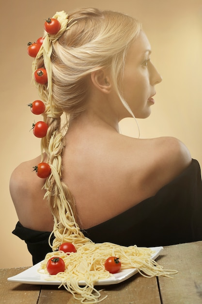 Mulher com tomate e espaguete no cabelo Foto gratuita