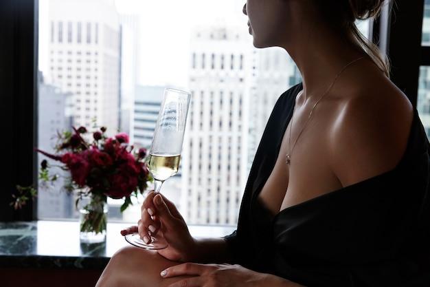 Mulher com túnica de seda preta com ombros opulentos e peito segura vidro com champanhe Foto gratuita