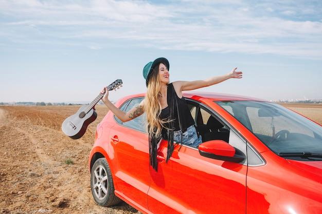 Mulher com ukulele na janela do carro Foto gratuita