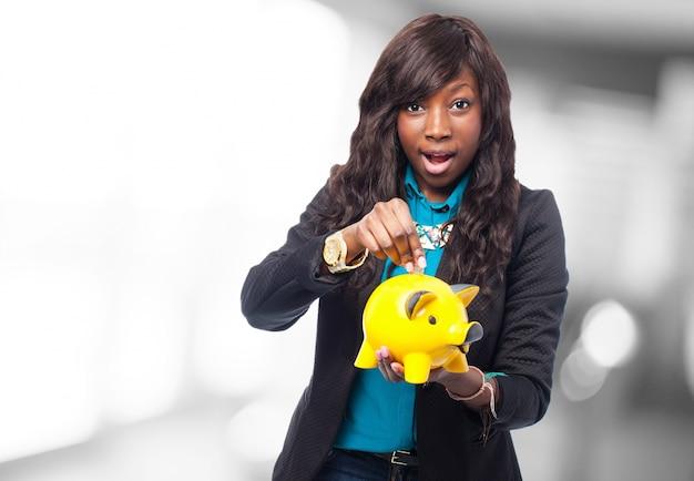 Mulher com um banco piggy amarelo nas mãos Foto gratuita