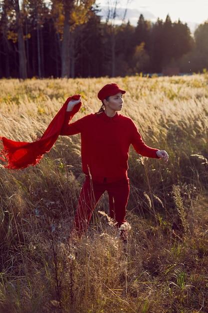 Mulher com um boné de suéter vermelho e lenço em pé em um campo no outono na grama alta e seca Foto Premium