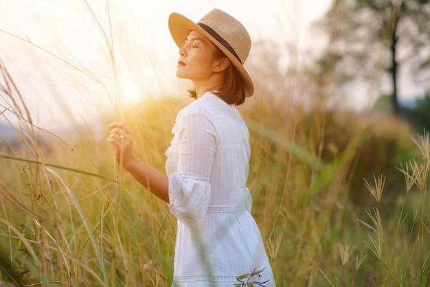 Mulher com um campo de grama à noite Foto Premium
