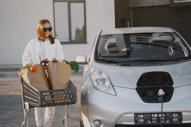 Mulher com um carrinho de compras de carro Foto gratuita