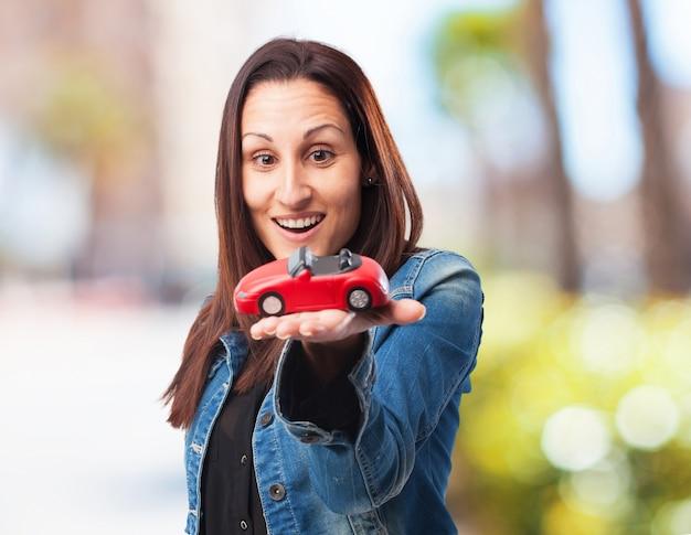 Mulher com um carro vermelho Foto gratuita