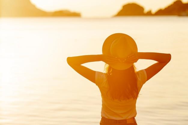Mulher com um chapéu ao pôr do sol na margem de um lago Foto gratuita