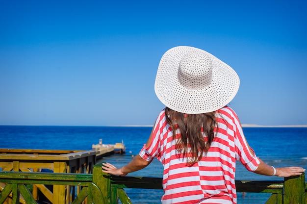 Mulher com um grande chapéu branco olha para o mar Foto Premium