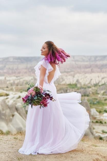 Mulher com um lindo buquê de flores nas mãos dela dança na montanha nos raios do pôr do sol do amanhecer. lindo vestido longo branco no corpo da menina. noiva perfeita com dança de cabelo rosa Foto Premium