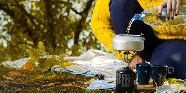 Mulher com um suéter amarelo despejando água para fazer café na floresta em um queimador de gás. fazendo café em um fogão primus na floresta de outono, passo a passo Foto Premium