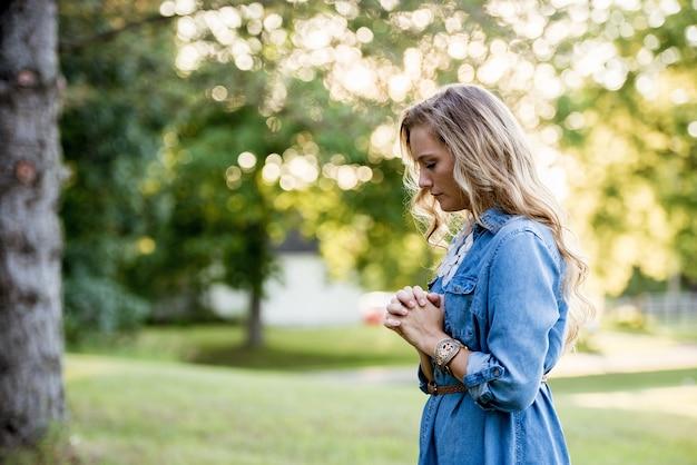 Mulher com um vestido azul e orando em um jardim sob a luz do sol Foto gratuita