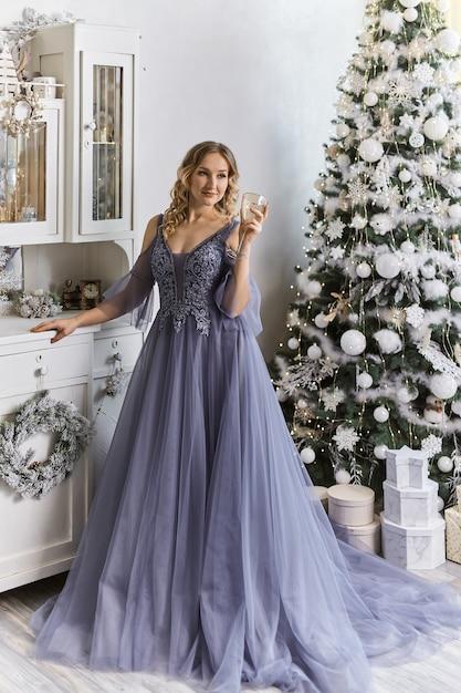 Mulher com um vestido festivo perto da árvore de natal Foto Premium